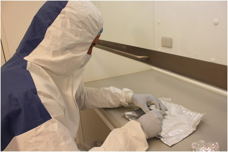 A person in a full body protective suit examines an artifact