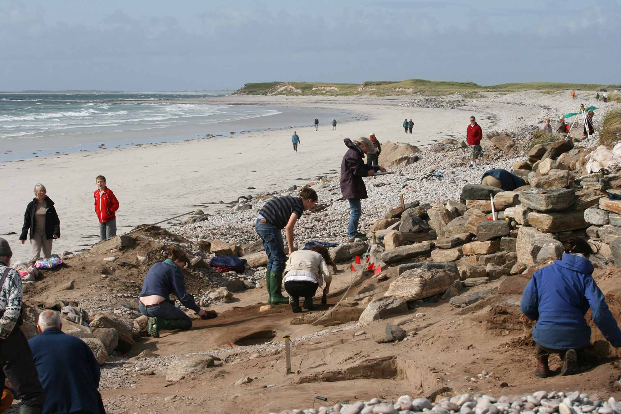 Archaeologists work at an excavation site on beach