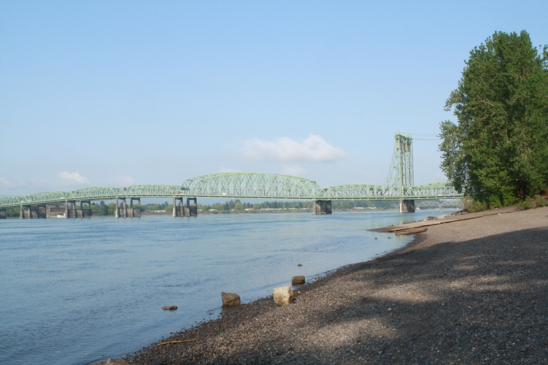 The Fort Vancouver waterfront today; a rocky river bank, and a wide river spanned by a steel raising bridge